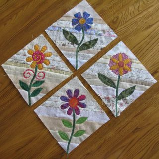 Applique flowers on string blocks