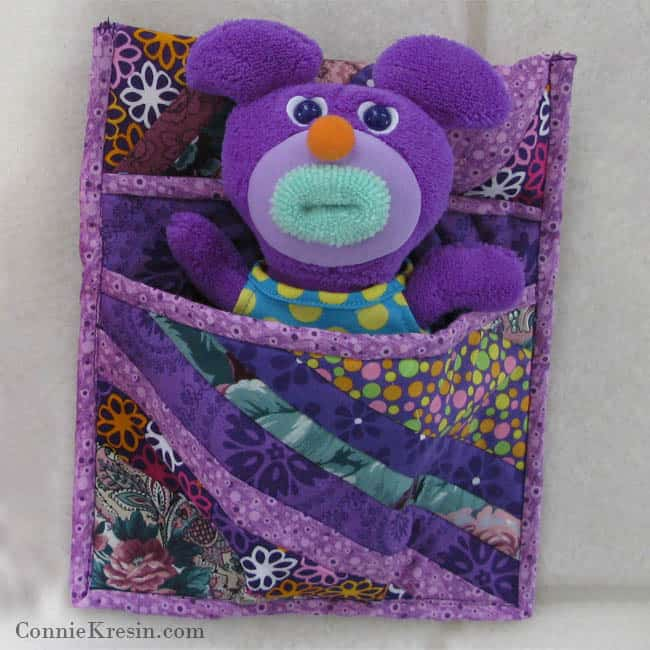 Purple sleeping bag with toy in it