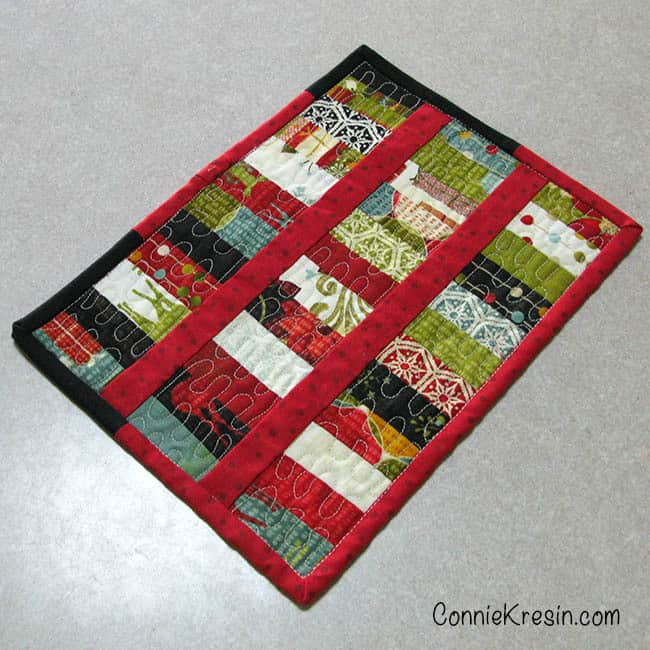 Scrappy Christmas Mug Rug tutorial made from leftover quilt scraps sewn together adding binding