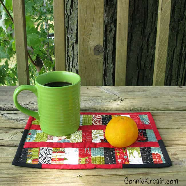 Scrappy Christmas Mug Rug tutorial with coffee cup on deck