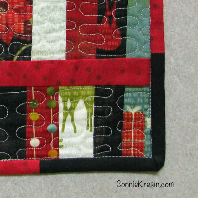 Scrappy Christmas Mug Rug tutorial closeup of machine stitched binding