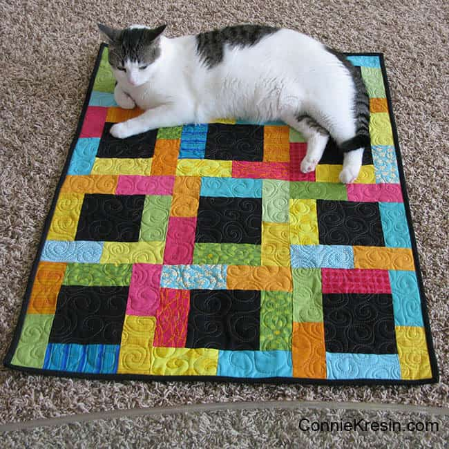Midnight Glow Quilt Tutorial quilt finished with a cat on it again