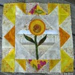 Scrappy Yellow quilt block with applique flower