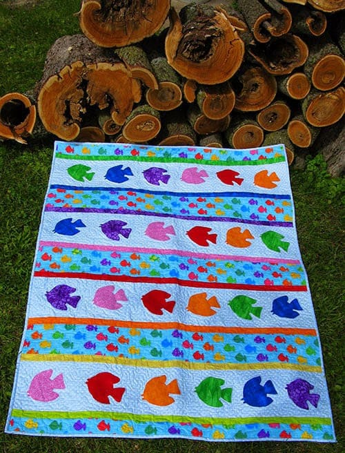 Go Fish quilt by the woodpile
