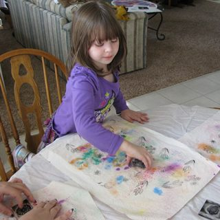 Child using stencils and paints on a shirt