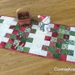 Mini Charm Christmas tablerunner easy to make in Christmas fabric with Christmas kitty on it