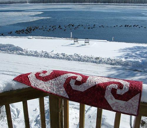 Red Snail Trail tablerunner in snow
