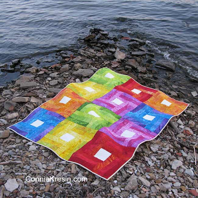 Rainbow Rail Fence baby quilt tutoral down by river on the rocks