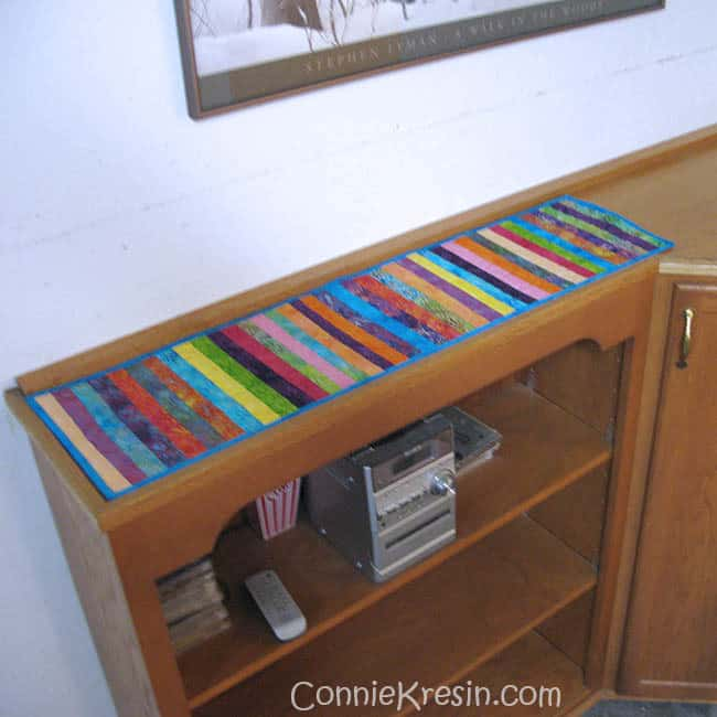 Narrow cabinet in the basement with string runner