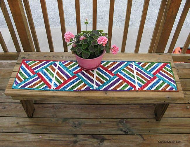 Bright Jewel strip pieced table runner on deck