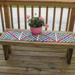 Bright Jewel strip pieced table runner on deck with flowers