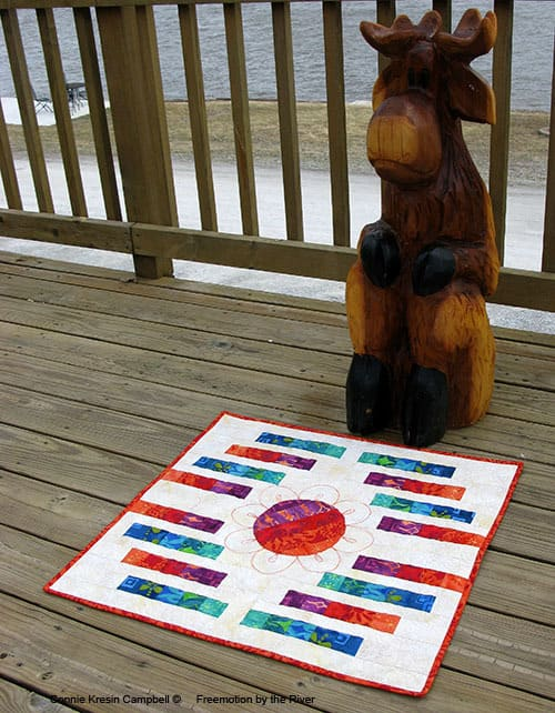 Woodcarved Moose called Bullwinkle on our deck with a quilt