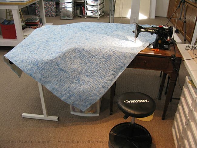 Supporting a quilt when free motion quilting on a domestic sewing machine