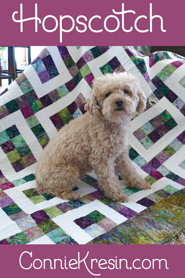Hopscotch quilt pattern done with different batiks and little Mickey sitting on it