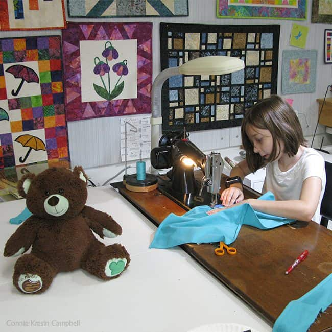 Kier Bear learning to sew on a vintage sewing machine