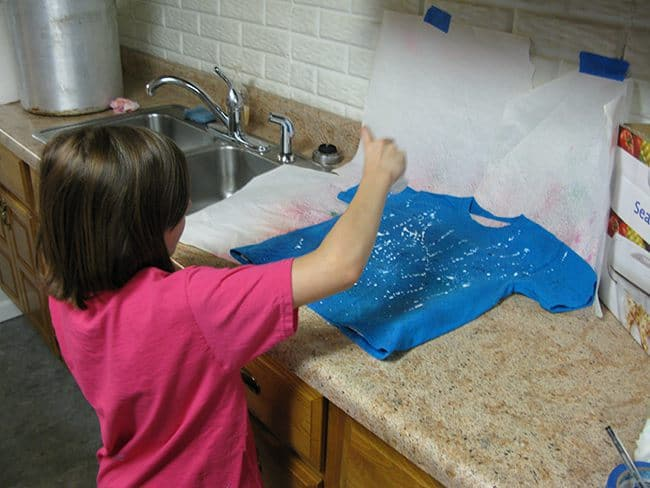 Spraying white fabric paint on a blue t-shirt