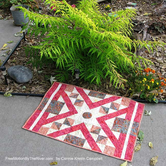 Indian Sunset quilt by a beautiful fern