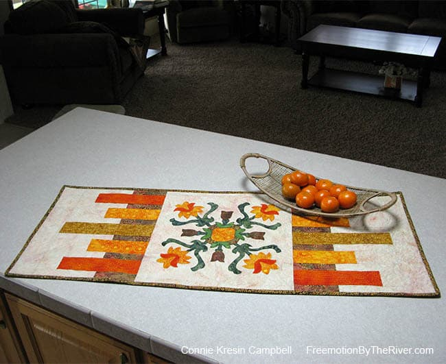 Folk Art Quilted Traditions table runner with a basket of oranges
