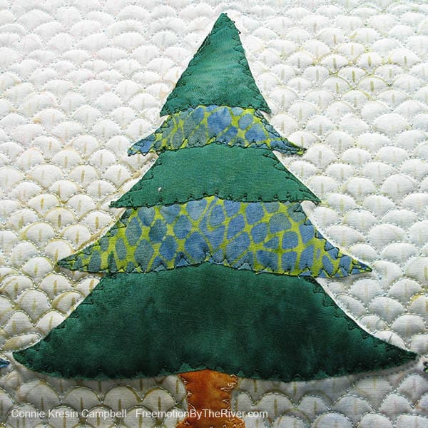 Freemotion applique done on batik evergreen tree wall hanging