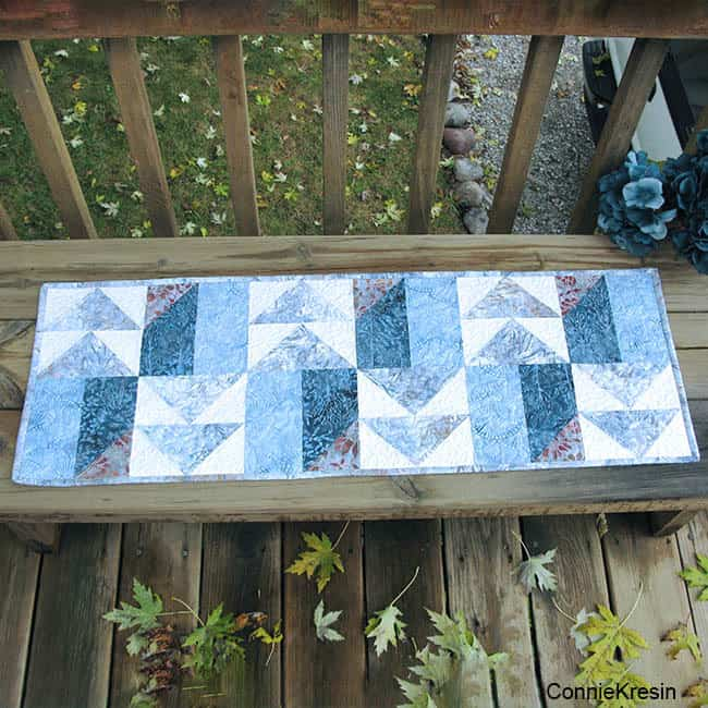 AccuQuilt Winter Blues table runner on deck bench
