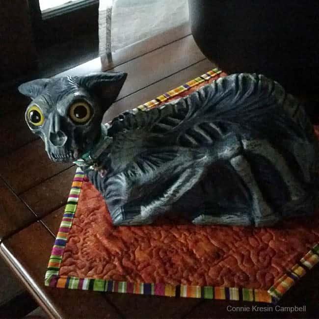 Creepy skeleton cat on table runner