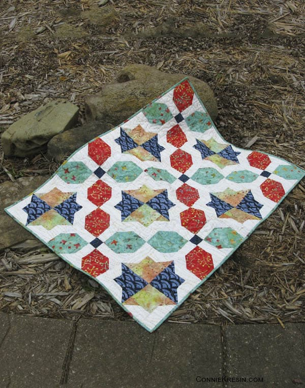 Morning Glory baby Quilt on rocks
