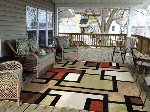 Deck with a outdoor rug on it