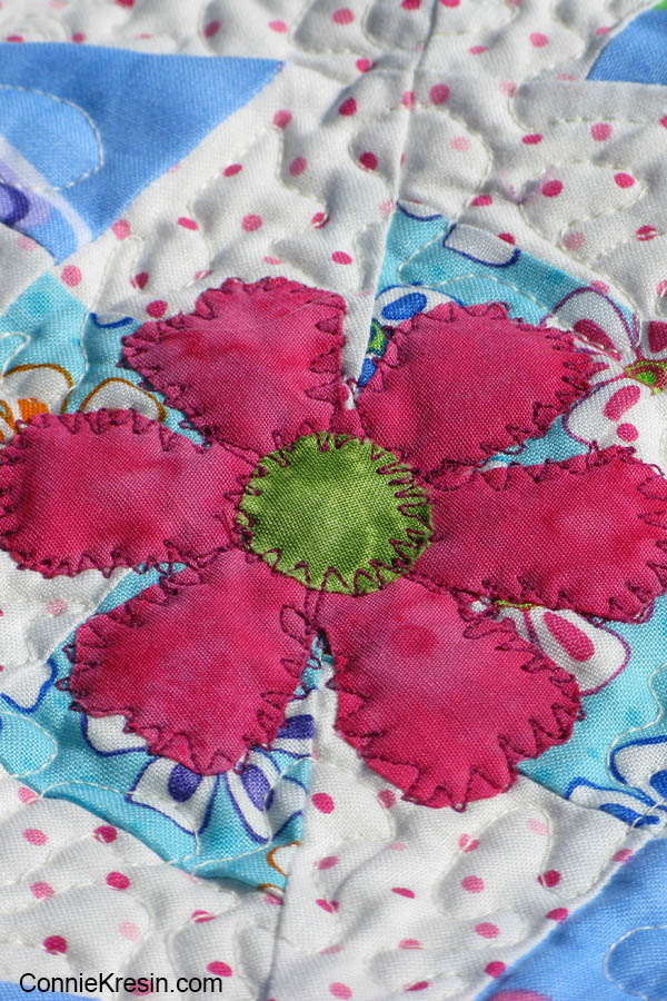 Lil Twister baby quilt with applique flower closeup