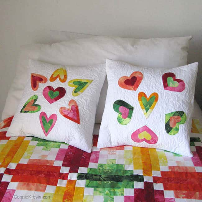 Heart applique pillow on bed with quilt