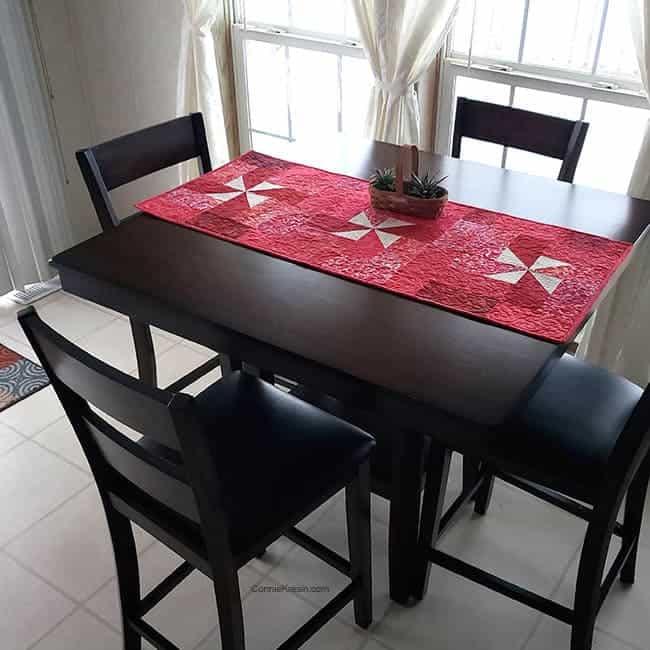 Red Pinwheel batik tablerunner on kitchen table