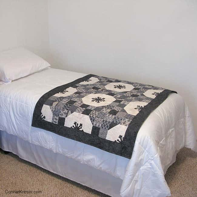 Alpine Snowflakes batik quilt on bed on bed