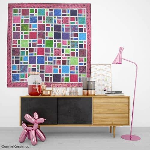 Scattered batik quilt on wall