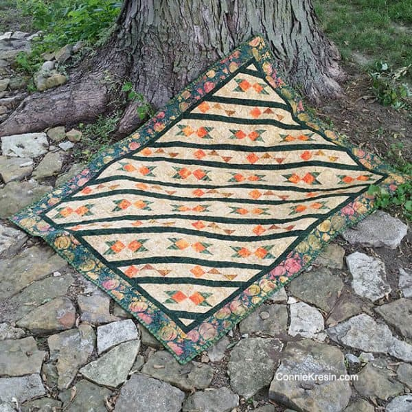 Arrowhead is a beautiful quilt shown in batiks from Island Batik. The pattern includes full-color diagrams to walk you through each step in creating this quilt. The pattern uses simple half square triangles and squares.