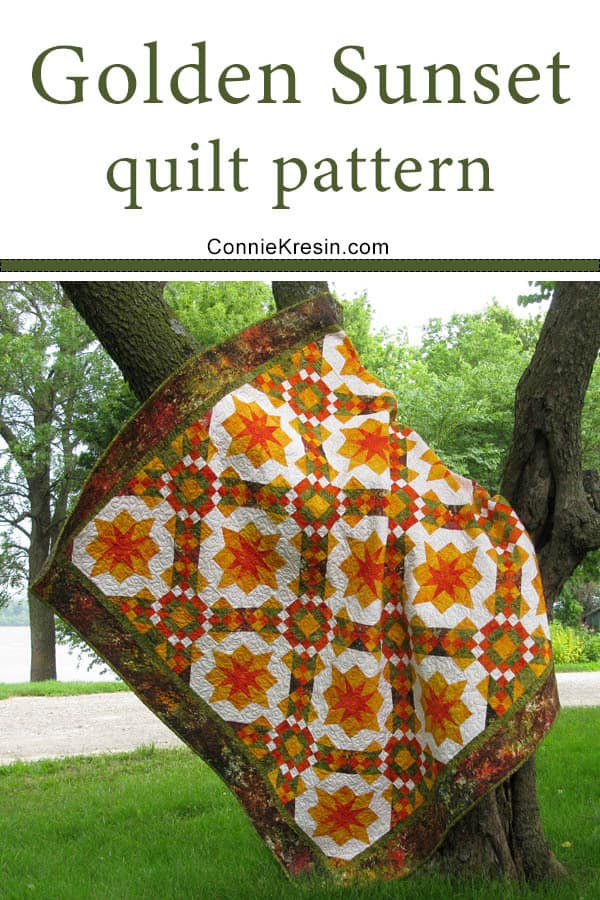 Golden Sunset quilt hanging in a tree by the river