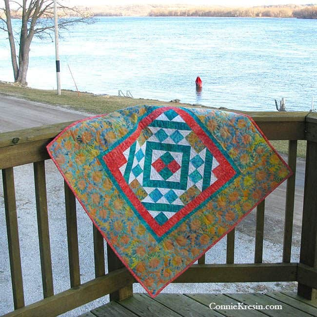 Diamond Maze Table Topper made with Island Batik fabrics on the deck and a buoy in the river
