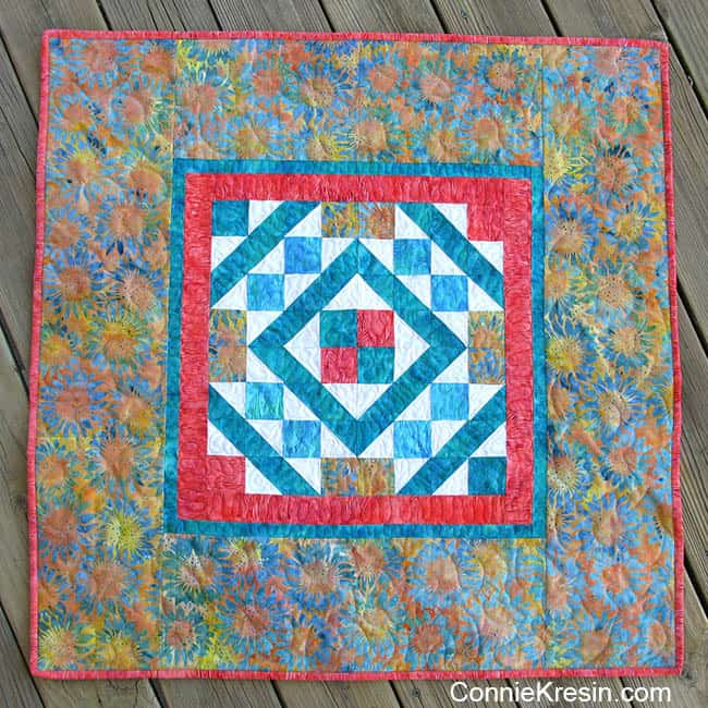 Diamond Maze table topper made with batiks on the deck