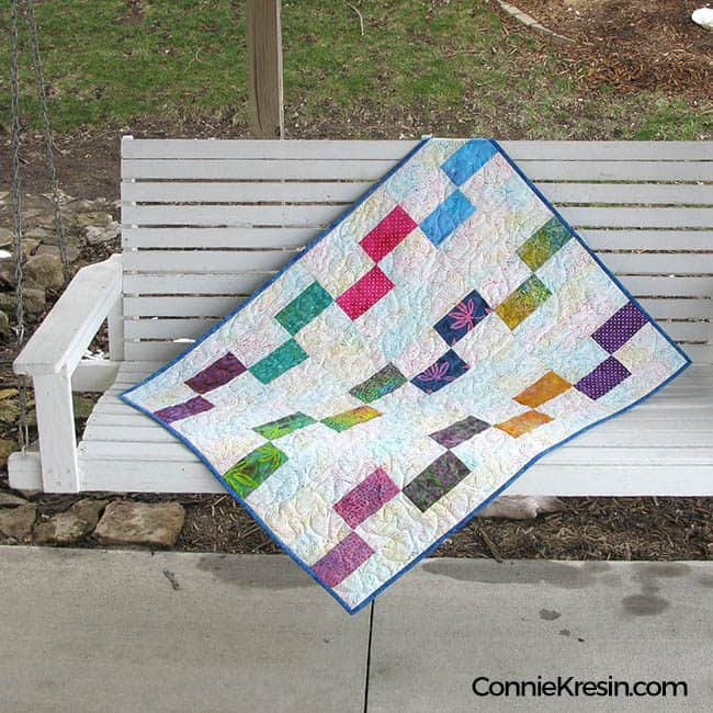 Batik baby Quilt on a swing outside