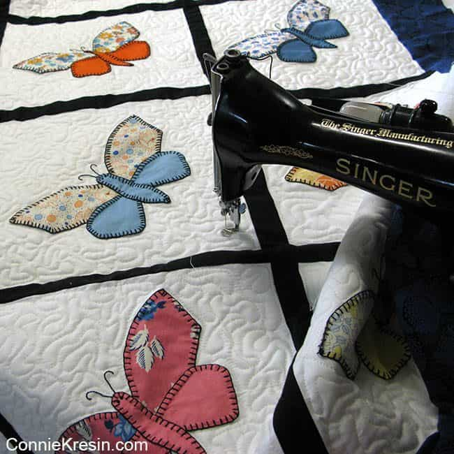Blue Antique Butterfly applique quilt being quilted