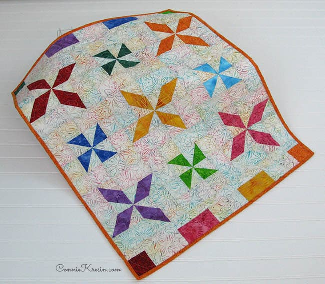 Tutorial for a beautiful fast and easy baby quilt made with batiks. It can be made with AccuQuilt dies or