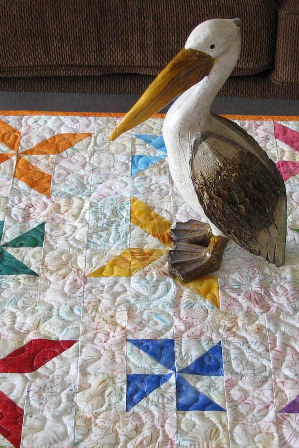 Pinwheel baby quilt with pelican
