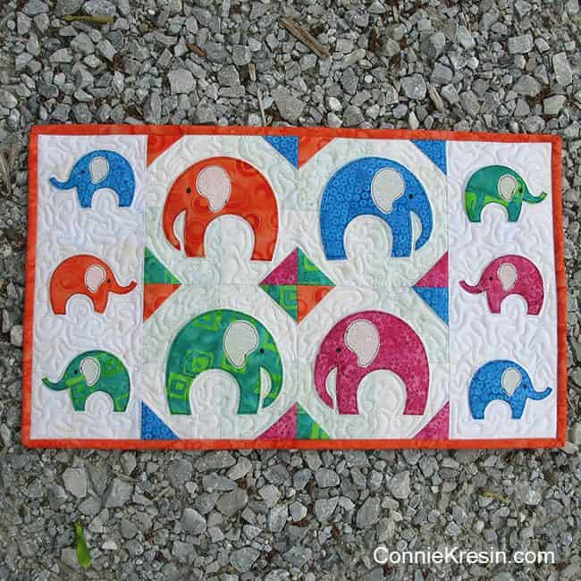 AccuQuilt GO! Elephant Walk wall hanging outside on gravel driveway
