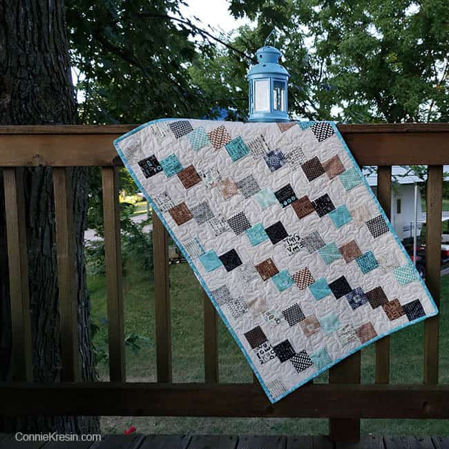 Mini Falling Charms quilted tablerunner on deck rail