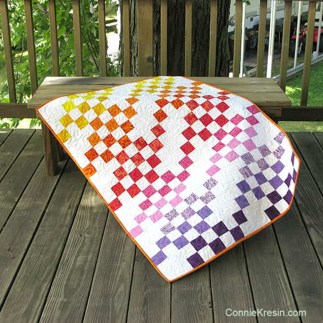 Rainbow Squares batik baby quilt on the deck bench
