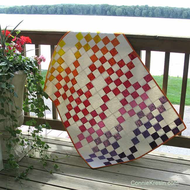 Rainbow Squares batik baby quilt on the deck sun