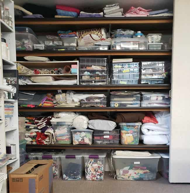 Quilt studio closet behind design wall with fabric and stash