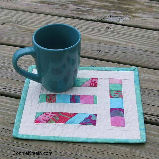 Teal angled strips mug rug quilt tutorial sitting on deck
