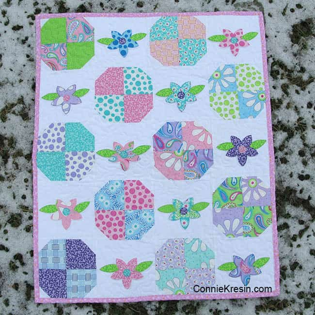 Floral applique baby quilt in the snow