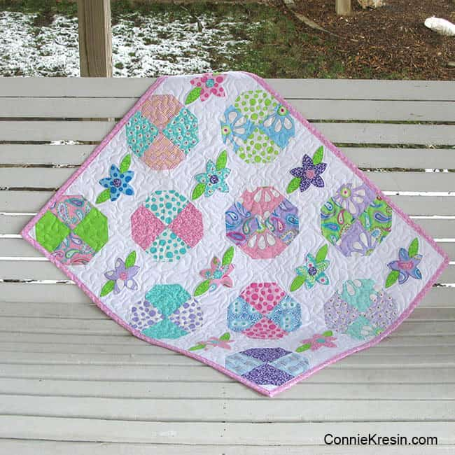 Floral applique baby quilt on a swing