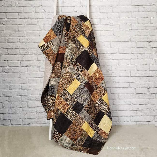 Stacks batik quilt hanging on a quilt ladder