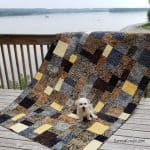 Stacks a beautiful batik quilt made with fat quarters of Wild Things from Island Batik with Sadie sitting on it
